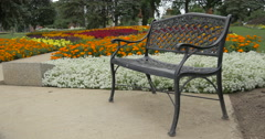 View of an iron bench near a flower bed at Kitchener, Canada Stock Footage