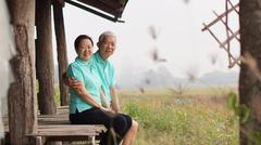 Asian senior couple sitting in the gazebo next to rice field Stock Photos