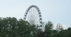 View of trees and a Ferris wheel spinning at Niagara Falls, Canada Stock Footage
