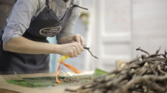 Girl in the studio preparing branches for Christmas wreaths Stock Footage