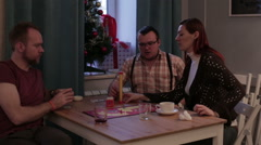 Cheerful people play a board game sitting Stock Footage