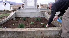 Man with a mattock dig the grave of his relatives to clean it of weeds 1 - stock footage