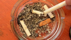 Ashes and cigarette butts are abandoned in an ashtray on the table - stock footage