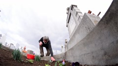 Man planted flowers on the grave of his relatives 1 - stock footage