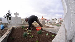Man planted flowers on the grave of relatives of his and red candle is lit 4. - stock footage