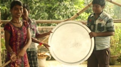 Stock Video Footage of An Indian girl hits a makeshift gong in slow motion