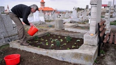 Man planted flowers on the grave of relatives of his and red candle is lit - stock footage