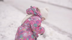 Little girl stands in a snowy park Stock Footage