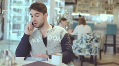 Young man talking on cell phone in cafe Stock Footage