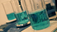 Glass flasks with blue liquid are mixed via magnetically stirred Stock Footage