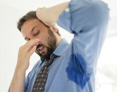 Business man with sweating under armpit in blue shirt Stock Photos