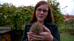 Woman hold a hedgehog in hand Stock Footage