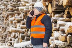 Stock Photo of Engineer talking on the smartphone near to piles of logs in winter