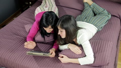 Two girlfriends looking online what to buy with tablet wide shot Stock Footage