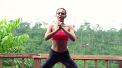 Young woman doing crouches on terrace with jungle view, slow motion, 240fps Stock Footage