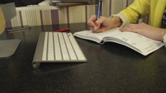 A student in a yellow jacket writing in a notebook Stock Footage