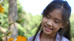 Happy little Asian girl looking flower in the garden Stock Footage