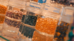 On the transparent surface are glass jars with colorful pills, candy Stock Footage