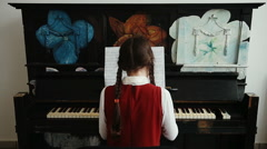 Girl playing the upright piano 1 - stock footage