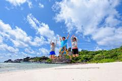 Happy family jumping on beach in Thailand - stock photo