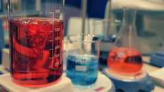 Glass flasks with red and blue liquid are mixed via magnetically stirred - stock footage