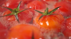 Cherry tomatoes above water surface, boiling in a pan, close up video Stock Footage