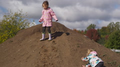 Two little girls playing on a giant sand heep. Stock Footage