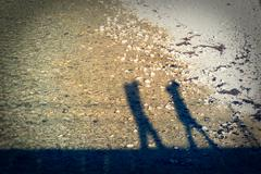 Shadow silhouette of a couple walking. - stock photo