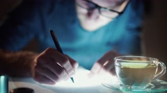 Man working at night, learning literature - stock footage