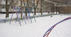 Stock Video Footage of Two Swings are Swinging Sandbox Playground Equipment Covered With Snow Childish