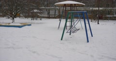 Metal Swing is Swinging Sandbox Playground Equipment Covered With Snow Childish - stock footage