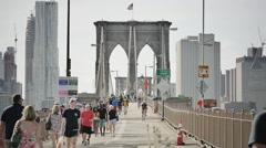 Brooklyn Bridge people bicycles New York City NYC skyline sunny day slow motion Stock Footage