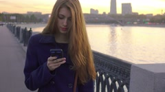 Pretty girl typing on smartphone walking on embankment of river. Stock Footage