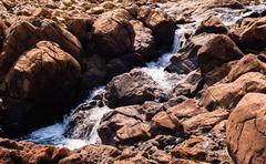 Stream flowing and splashing among bare red rocks - stock photo