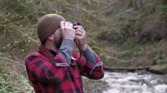 Hiker in woods taking photos Stock Footage