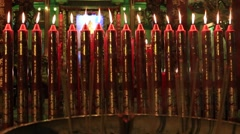 Red wax candles and incense sticks burning in Buddhist temple. Bangkok, Thailand Stock Footage