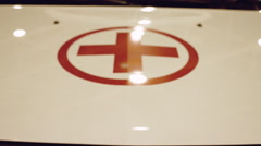 The red cross on the hood of the ambulance and reflection flashing beacons Stock Footage