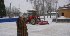 Tractor Moves Along a New Year's Tree in Park Konotop Red Tractor is Cleaning a Stock Footage
