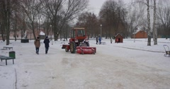 Two Teenage Boys Are Walking by Park Konotop Tractor Red Bulldozer is Cleaning Stock Footage