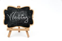 Wooden easel mini blackboard with text WEDDING - stock photo
