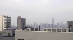 Manhattan skyline from Brooklyn rooftop scanning across buildings skyscrapers NY Stock Footage