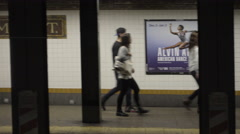 L train pulling into subway station, people walking on platform across tracks NY Stock Footage