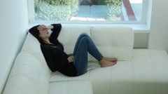 Woman with very strong headache lying on sofa at home 4K Stock Footage