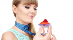 Woman holds cupcake trying to resist temptation 4K - stock footage