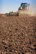 tractor cultivator raises great dust on soil - stock photo