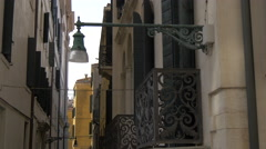 Old street lamp on a building with decorated balconies in Venice Stock Footage