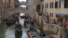 Gondoliers paddling gondolas under a small bridge in Venice Stock Footage