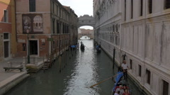 Rowing gondolas on Rio de Palazzo, under the Bridge of Sighs in Venice Stock Footage