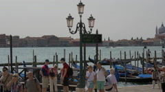 People walking by a gondola station in Venice Stock Footage