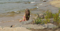 View of a girl sitting and playing on the lake shore at Killbear Provincial Park Stock Footage